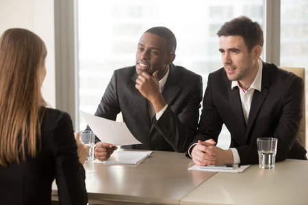 Afro american company leader with caucasian hiring manager listening and reviewing female job applicant after reading resume or CV. Multinational employers asking question to woman on job interview