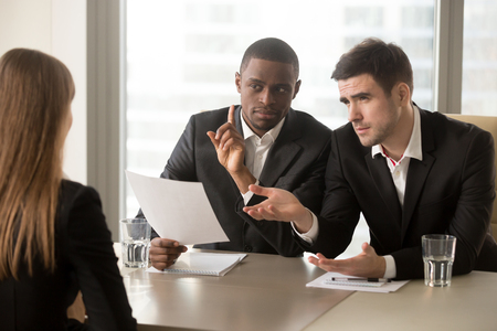 Demanding multinational recruiters meticulously examining female job candidate with asking difficult questions. Woman giving wrong or bad answers on job interview. Applicant questionable qualification Stock Photo
