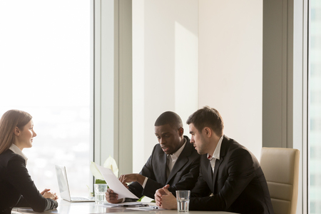 African american employer discussing candidates resume with caucasian colleague, reading and pointing on important CV information. Nervous young female applicant waiting on decision at job interview
