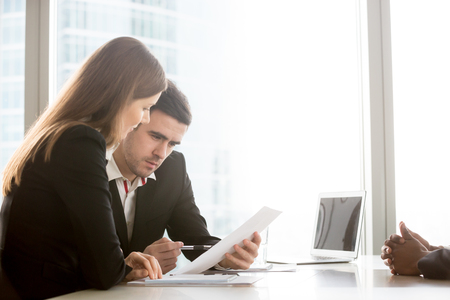 Caucasian female and male recruiters carefully reading african american candidate resume, business partners analyzing agreement document, studying important terms in text of contract. Job interview