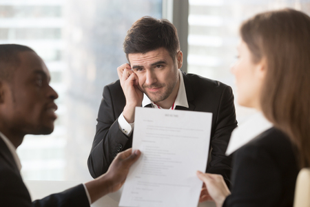Worried male job candidate interested in company vacancy anxiously looking on multinational recruiters analyzing and discussing his resume on interview. Unconfident applicant waiting hiring decision