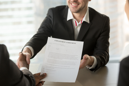 Boss or human resources manager handshaking with male job candidate, offering employment agreement document. HR manager congratulating new company worker after successful job interview. Close up view