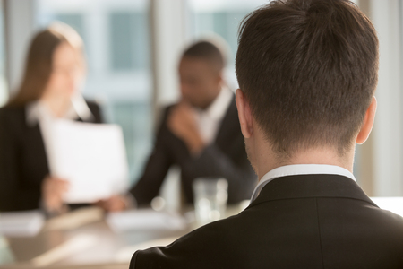 White male job candidate waiting for employers decision, multinational HR managers analyzing resume on background. Man in formal wear interested in vacancy visiting job interview. Close up back view Stock Photo