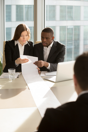 African american male and caucasian female employers reading with confusion huge resume, multinational lawyers studying long list of client claims, partners shocked with number of contract conditions