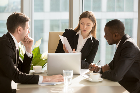 Confident caucasian businesswoman showing document with financial indicators, presenting project to african american colleague during negotiations in meeting room at office. Planning business strategy conference table 스톡 콘텐츠