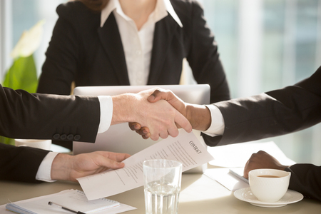 Multi-ethnic businesspeople shaking hands at negotiation table after singing contract in presence of female secretary, notary or lawyer. Strong handshake between partners making good deal. Close up
