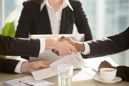 Empresários multi-étnica, apertando as mãos na mesa de negociação depois de cantar contrato na presença de secretária, notário ou advogado feminino. Forte aperto de mão entre os parceiros, fazendo um bom negócio. Fechar-se Foto de archivo