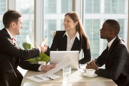 幸せな女性の会社のリーダーは、巧妙な交渉および契約締結後満足する実業家と手を振って、彼女のアフリカ系アメリカ人パートナーと机に座って 写真素材