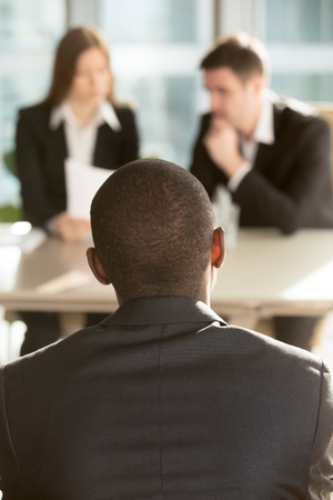 African american male job candidate waiting for hiring decision on job interview, caucasian employers reading resume on background. Millennial black man interested in vacancy searching his first job Фото со стока - 87738202