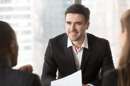 Portrait of confident job candidate talking with multinational interviewers in office, professional specialist communicating with hiring managers. Smiling businessman talking with business partners Stock Photo