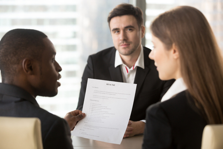Rear view african american company leader analyzing and discussing applicants resume with female hr specialist, caucasian male job candidate waiting for hiring decision after interview on background Stock Photo