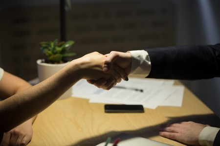 Two businesspeople shake hands to seal a deal, recruiter employing new staff member, human resources manager shaking hands with job candidate after interview. Close up side view. Handshake concept. Stock Photo