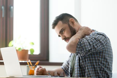 Troubled bearded man massages aching neck with a pained expression, working on laptop computer, deep in thoughts. Stock Photo
