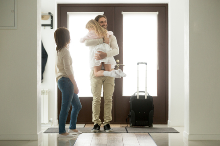 Happy father arrived home returning after business trip with baggage, daddy missed little daughter holding in arms hugging girl while wife standing in hall, family reunion, welcome back dad concept