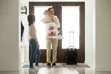 Feliz padre llegó a casa regresando después del viaje de negocios con equipaje, papá se perdió a la pequeña hija sosteniendo en brazos a la chica mientras que la esposa de pie en el hall, reunión familiar, Bienvenido a volver concepto de papá Foto de archivo