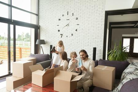 Jonge gelukkige familie met kinderen dozen uitpakken samen zitten op de sofa in de moderne woonkamer van het landhuis verplaatsen regelen in een nieuw huis, kinderen helpen ouders om dingen in te pakken verplaatsen verhuizen