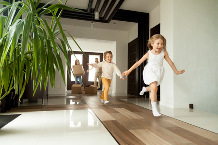 Happy young family with cardboard boxes in new home at moving day concept, excited children running into big modern own house hallway, parents with belongings at background, mortgage loan, relocation Foto de archivo