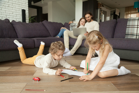 Children little boy and girl having fun on warm floor, boy playing toy car, girl drawing with colored pencils, parents using laptop at home, family leisure together in living room, underfloor heating Banco de Imagens