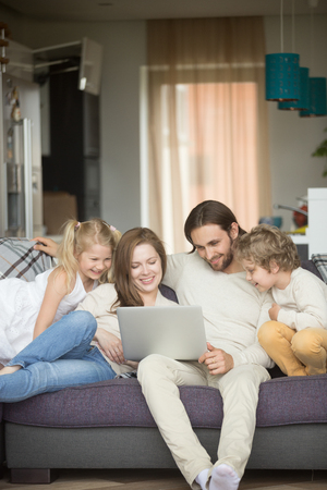 Family with children having fun using laptop sitting on sofa at home, parents and son daughter relaxing on couch holding computer, man woman with kids smiling watching funny video online, vertical Stock Photo
