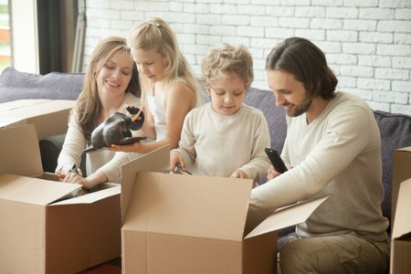 Happy family of four with two kids unpacking boxes moving into new home, smiling children helping parents with belongings in open cardboards sitting on sofa in living room together after relocation
