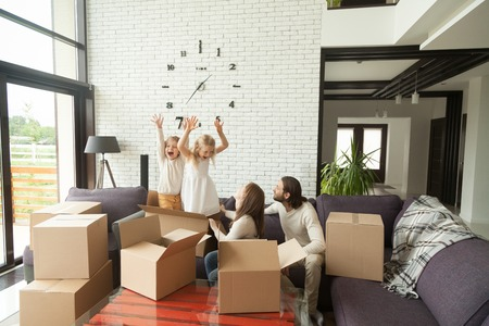 Happy married couple with kids playing while packing unpacking in modern living room interior, cheerful family and children having fun with boxes on couch together at moving day, move in out new home Stock Photo