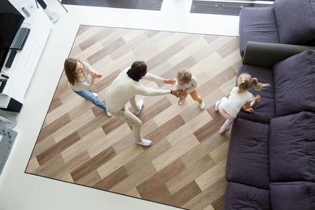 Family playing hide and seek game at home, mother and kids hiding clapping hands while blindfolded father seeking catching children wife, parents and son daughter having fun in living room, top view Stockfoto