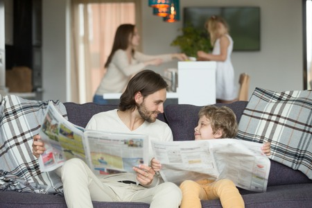 Happy dad and son reading newspapers together on couch, father with little boy looking at each other holding paper news, funny kid copying imitating daddy sitting at home on sofa, intelligent child Banco de Imagens