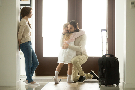 Sad father hugging little daughter before leaving for long business trip, upset dad embracing crying girl saying goodbye to daddy at home in hall with baggage, family separation, good bye, farewell 版權商用圖片