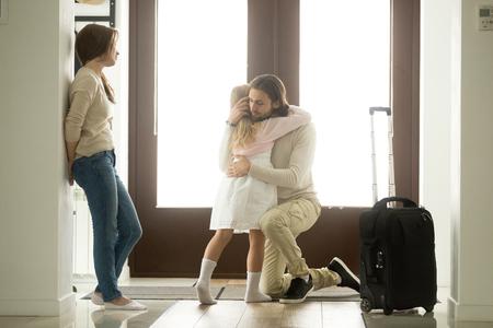 Triste padre abrazando a su pequeña hija antes de partir para un largo viaje de negocios, molesto papá abrazando a una niña llorando diciéndole adiós a papá en casa en el pasillo con equipaje, separación familiar, adiós, adiós
