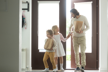 Happy father with kids coming back home holding paper bag, little son helping dad to carry packets returning from store market, daddy and children after grocery shopping together, family buying food Stock Photo