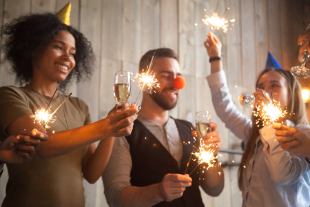 African and caucasian friends holding sparklers celebrating New year party, diverse people in funny hats hanging out together with champagne glasses on holiday eve, multiracial guys enjoy celebration