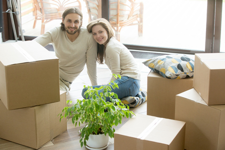 Moving day, happy couple looking at camera sitting on the floor bonding with boxes belongings, young first time homeowners enjoying new home, buying real estate, move in out and relocation concept Stockfoto