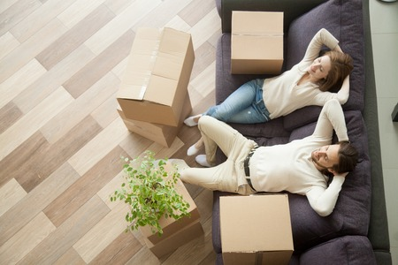 Couple resting on couch after moving in, man and woman relaxing on sofa just moved into apartment with cardboard boxes on floor, happy satisfied homeowners enjoying first day in new home, top view Standard-Bild