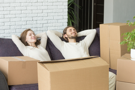 Happy couple relaxing on sofa with boxes, relaxed man and woman resting on couch hands behind head on moving day, dreaming of future in new own home, delivery service for easy move concept Stock Photo