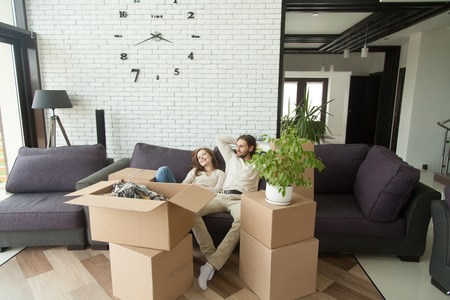 Young couple relaxing on couch just moved into new home with cardboard boxes, happy man and woman packed belongings sitting on sofa in living room, moving delivery service and relocation concept Banco de Imagens