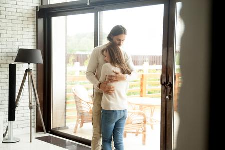自宅のインテリアに立って抱き合う若い男女、優しい夫が優しく妻を抱きしめ、愛とサポートを示し、カップルの和解の概念、人間関係の理解、メ 写真素材