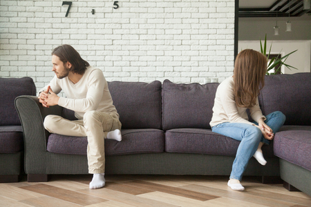 Unhappy sad couple sitting apart on couch in living room after quarrel, frustrated man and woman turning their back ignoring having conflict at home, can not find compromise, misunderstanding concept Stock Photo - 91101347