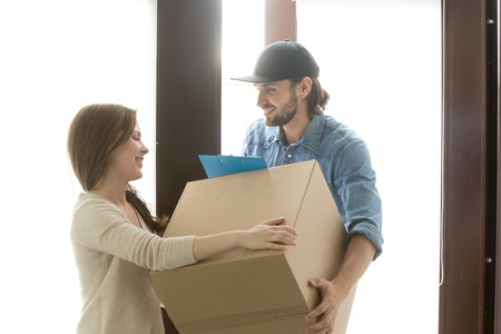 Delivery service concept, woman receiving cardboard box from man at home standing in hallway door, customer taking package accepting postal parcel, courier delivering container to recipient
