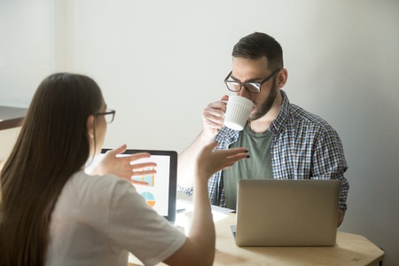 Business meeting of millennial employees. Beautiful businesswoman in glasses explains to coworker concept of job. Businessman listening and drinking coffee.