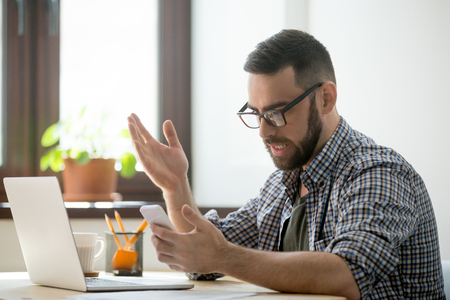 Confused bearded manager in glasses is angry because mobile phone is discharged. Millennial businessman in casual receiving bad news and spam in smartphone