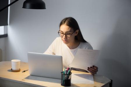Jong toevallig onderneemsterholding document document en het werken aan laptop in huisbureau in avond. Geconcentreerde vrouwelijke werkgever die overeenkomst controleert op het werk.