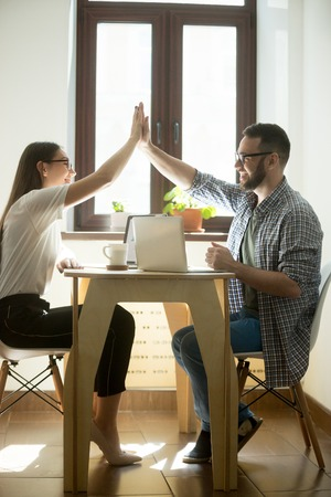 Millennial colleagues giving high fives while finishing working project in business office. Two happy successful young managers, winning concept. Vertical image
