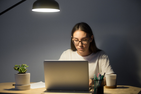 Portrait of millennial businesswoman in glasses looking at laptop and working at night. Concentrated female manager using computer in home office in evening Stock Photo