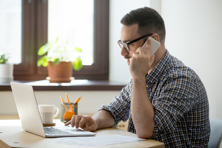 Young confident manager working on laptop and talking on smartphone. Millennial manager speaking with customer on cellphone and typing on computer in office. 스톡 콘텐츠