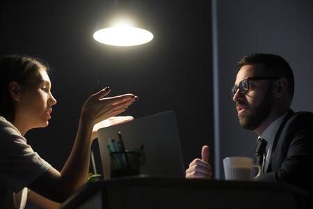 Twee millennial ondernemers bespreken werkproblemen bij nachtdienst. Zakenman en onderneemsterzitting bij Desktop en het oplossen van baanvraag. Overwerk concept Stockfoto