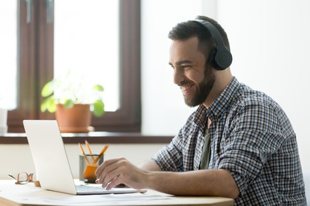 Handsome man with beard listening music in headphones and looking on screen of laptop. Young manager having a rest and playing in computer games or making video call on pc
