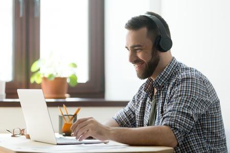 Hombre hermoso con música que escucha de la barba en auriculares y mirada en la pantalla de la computadora portátil. Gerente joven descansando y jugando en juegos de computadora o haciendo videollamadas en la PC Foto de archivo
