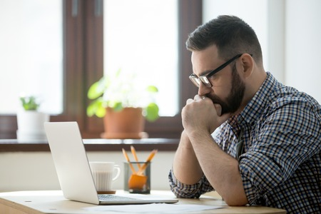 Young bearded manager working and reading data on laptop in home office. Thoughtful casual businessman thinking about job and looking on screen of notebook