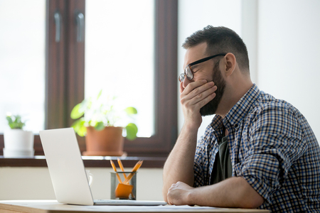 Exhausted millennial businessman in casual wear yawning at workplace in home office. Fatigued young employee wants to sleep at job Stock Photo