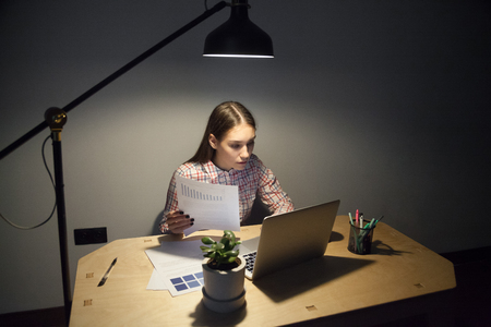 Millennial businesswoman looking on screen of laptop and comparing new data with business plan. Overwork, overhours, deadline, night shift concept in dark home office.